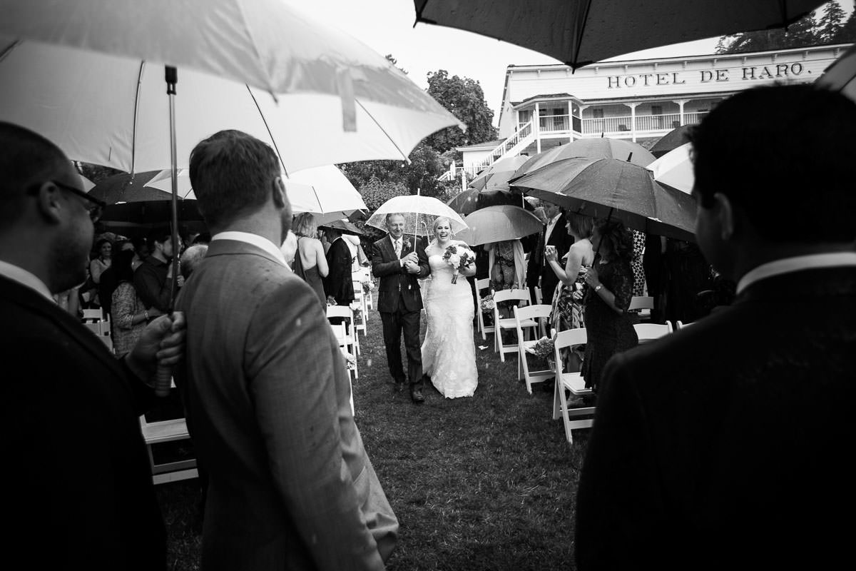 Happy bride walking down the aisle in the rain