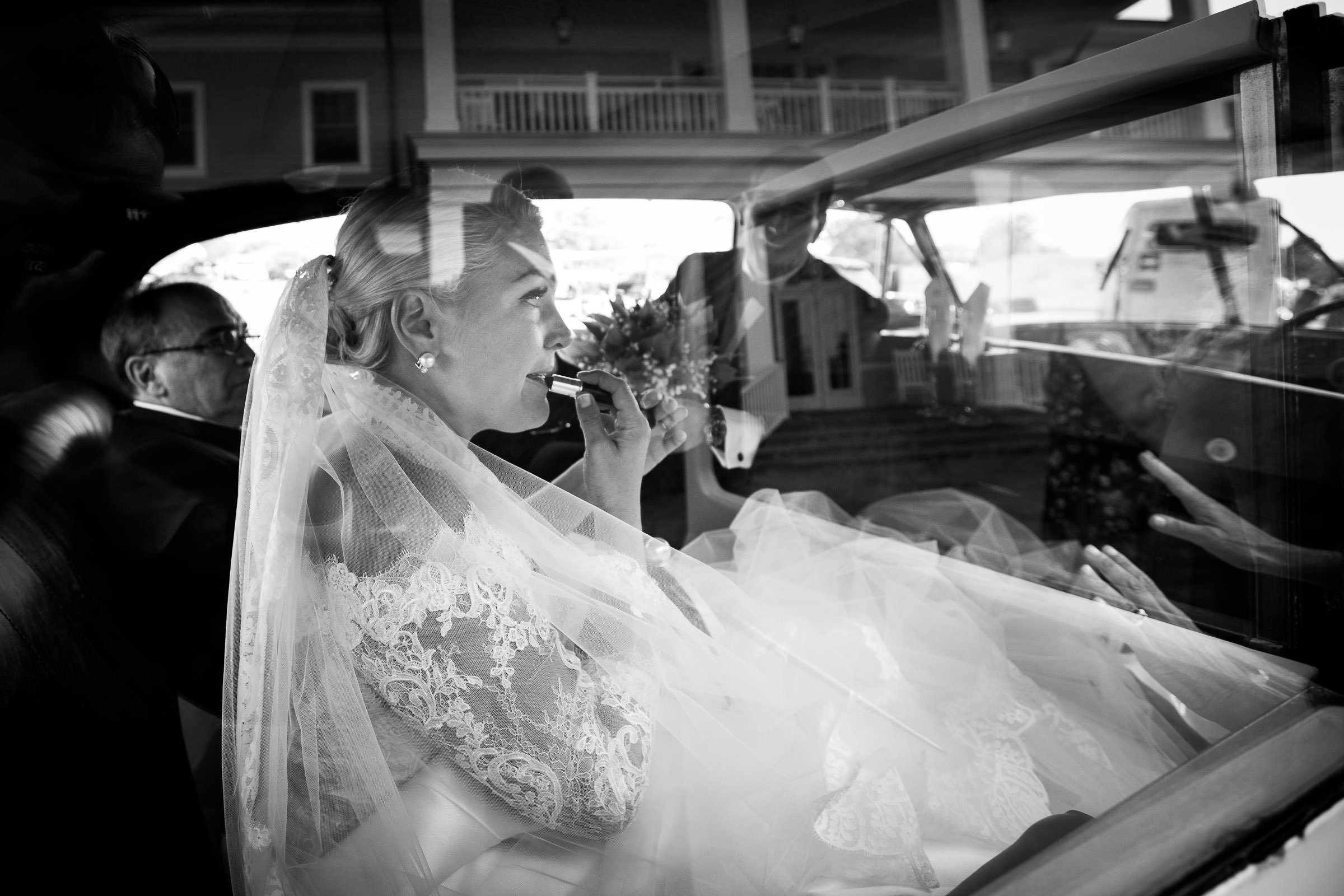 bride putting on lipstick in the car