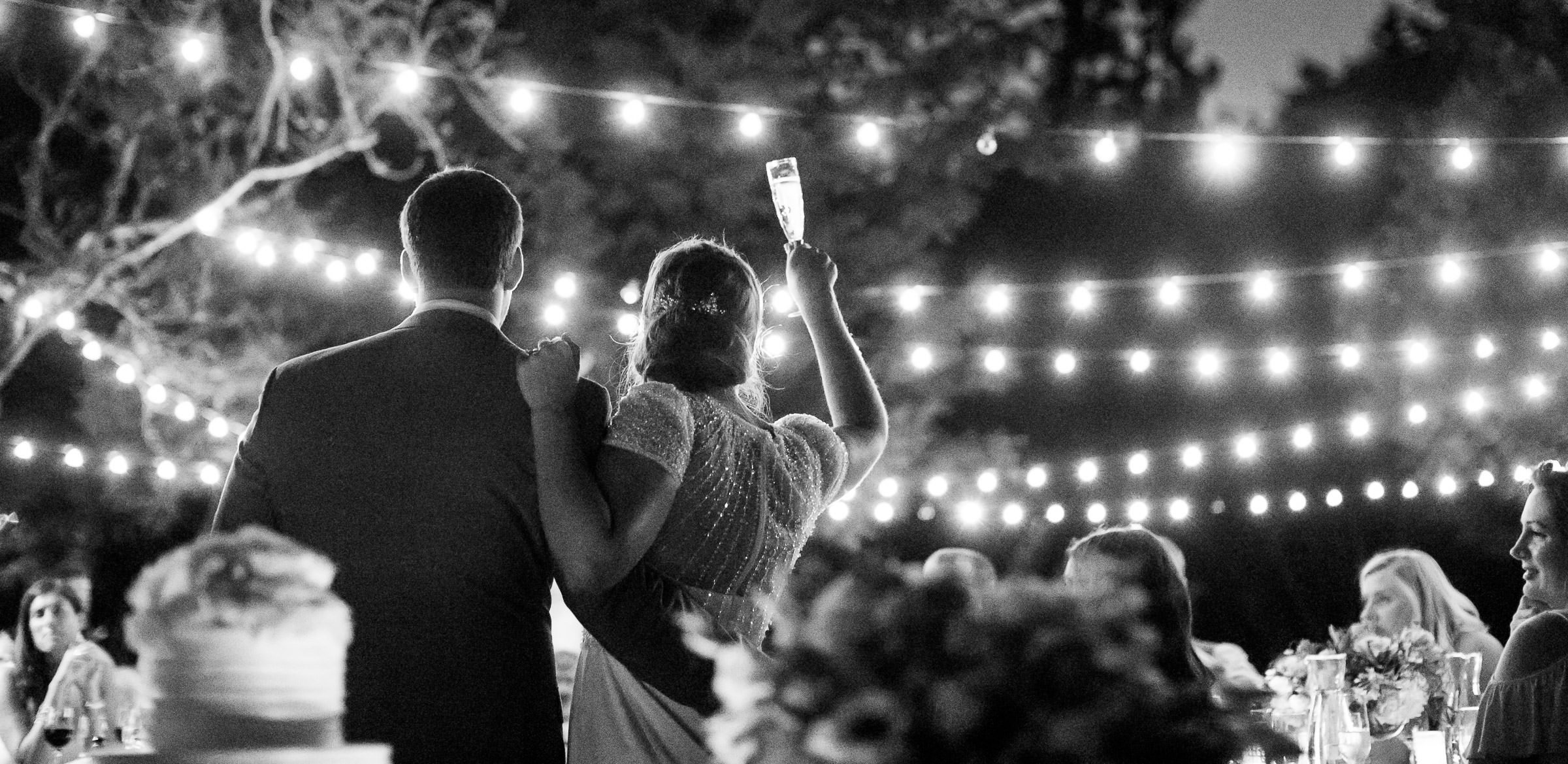 bride and groom toasting at night