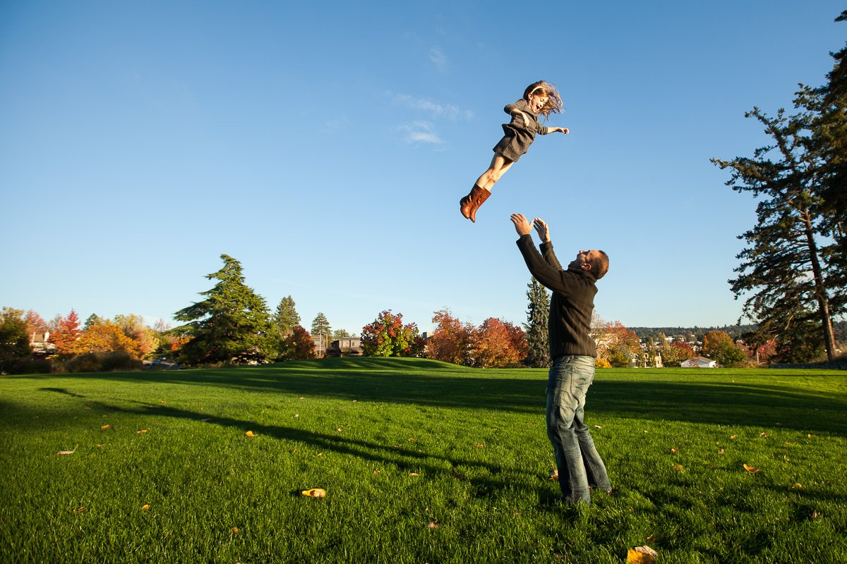 father throwing daughter into the air
