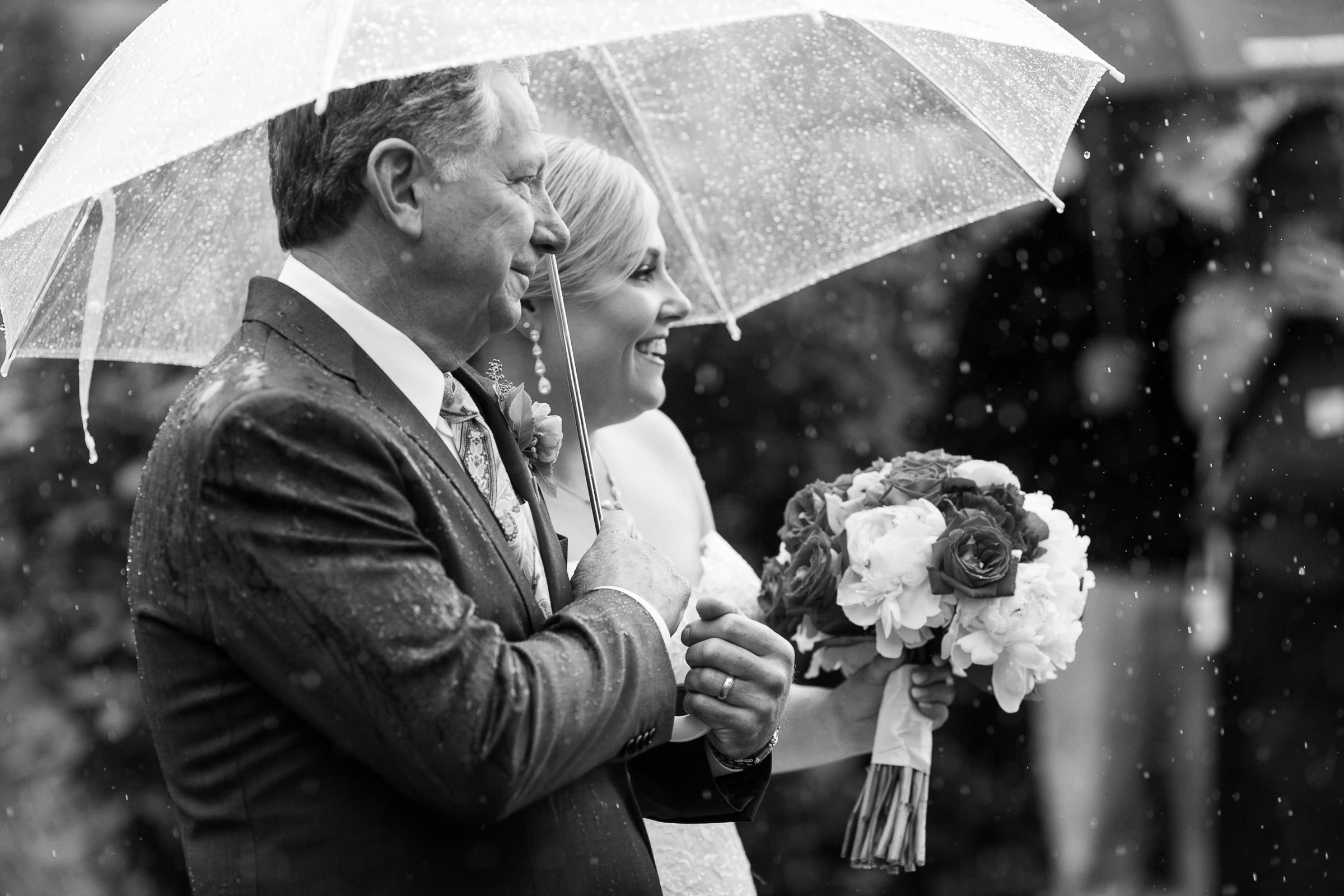 bride with her father in the rain during ceremony