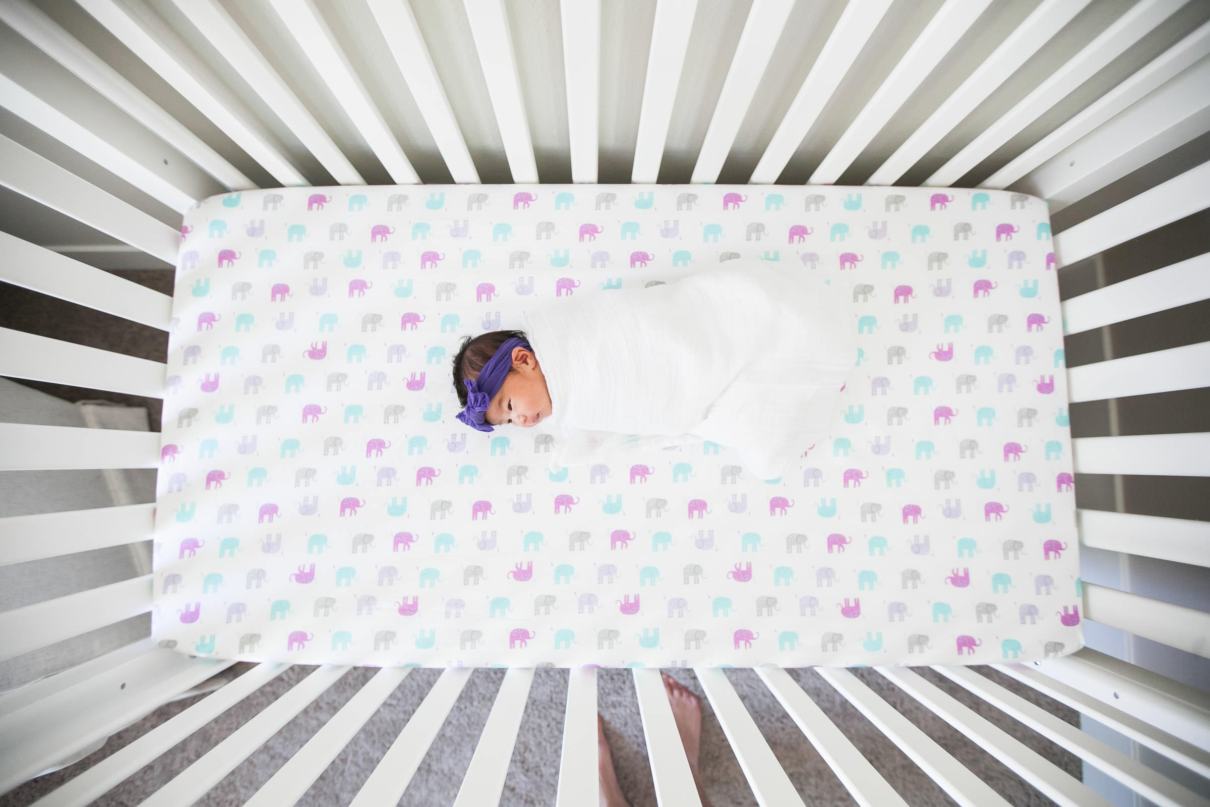 swaddled baby sleeping in her crib