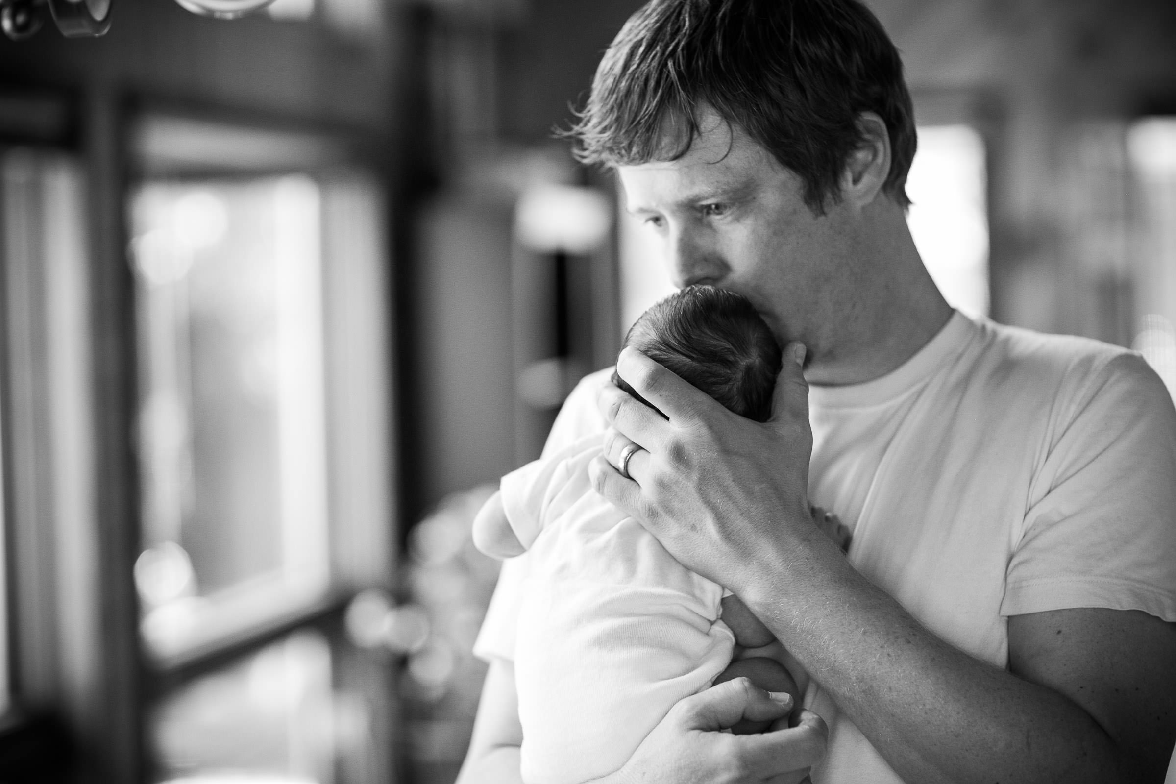 father kissing newborn on head