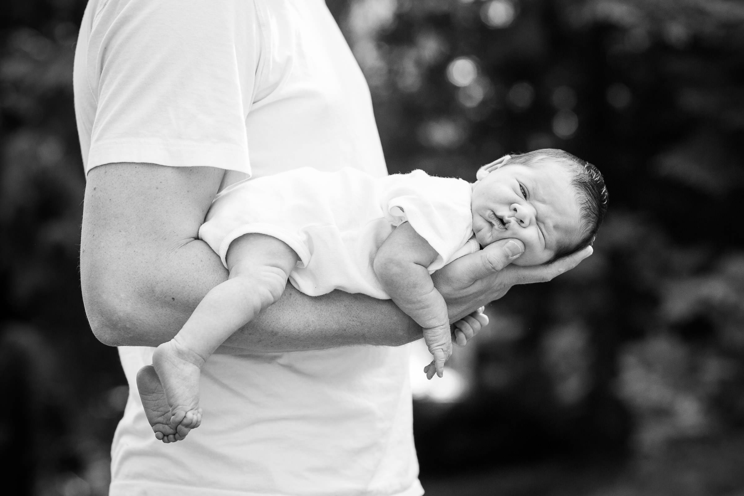 dad holding sleeping baby in one arm