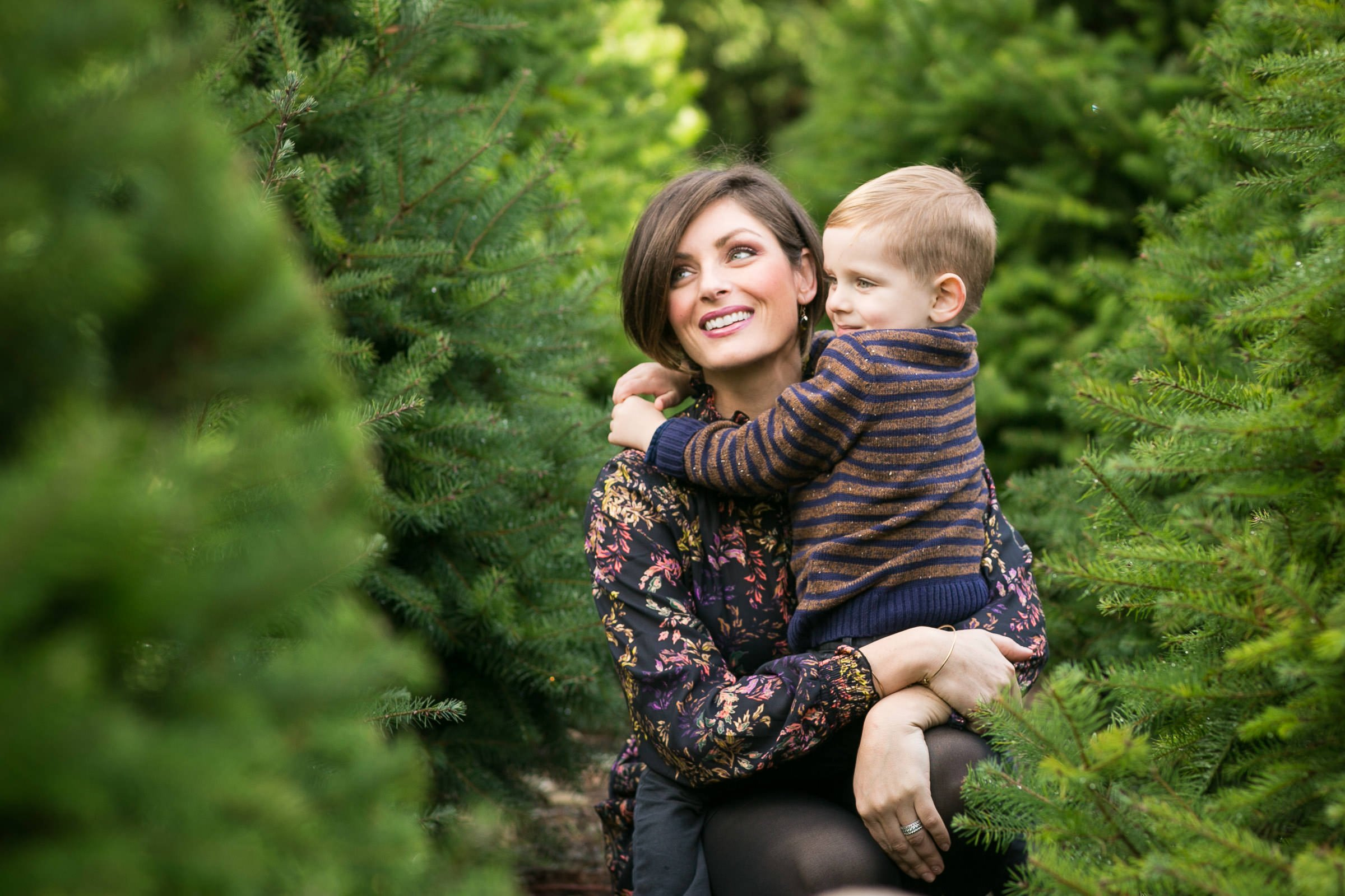 mother and son sitting among evergreen trees
