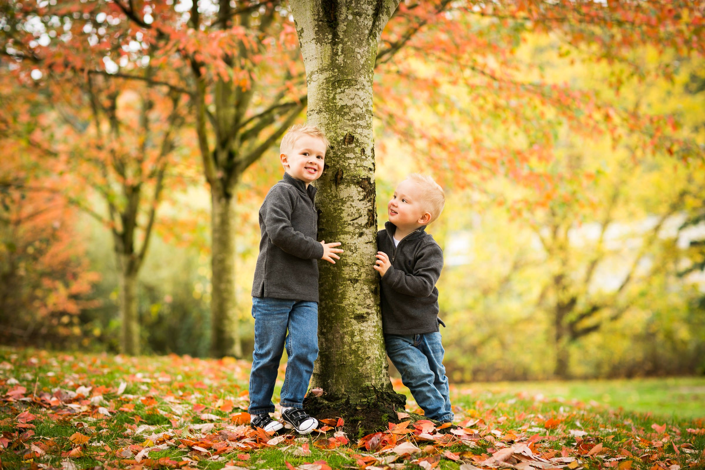 brothers playing under a tree with fall color