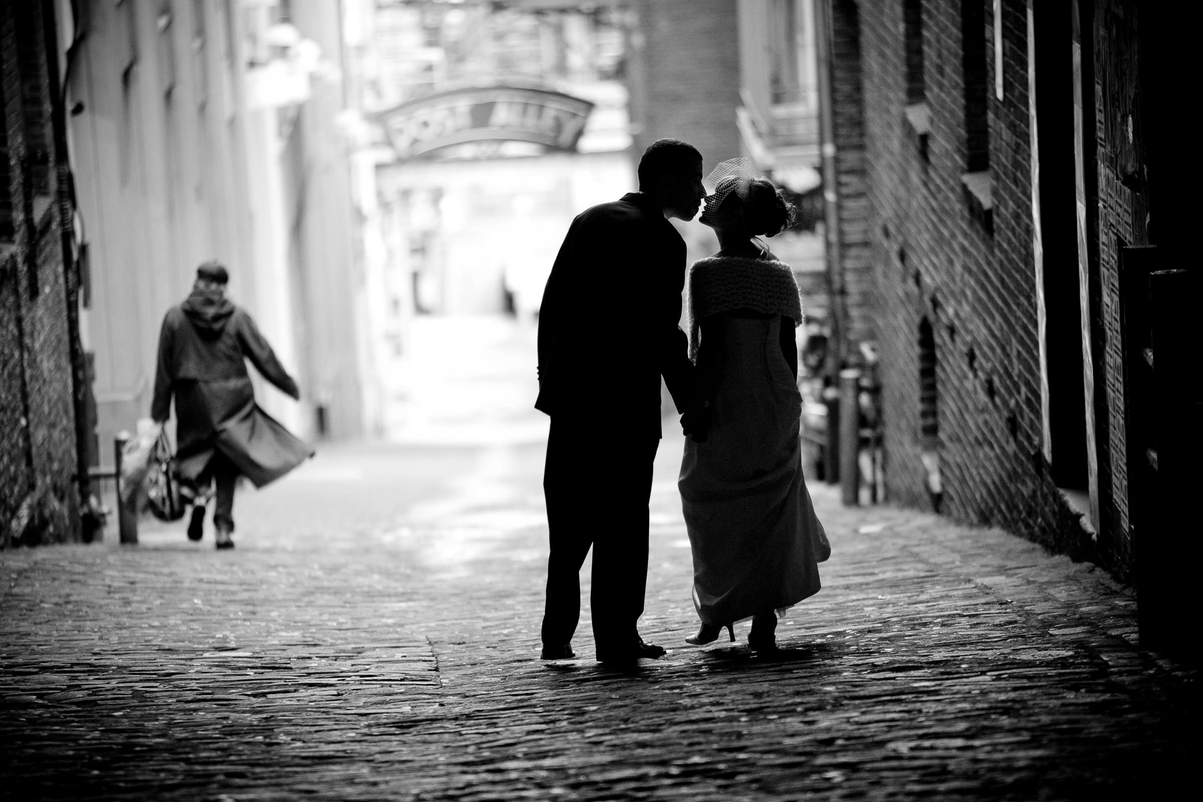 bride and groom kissing in post alley