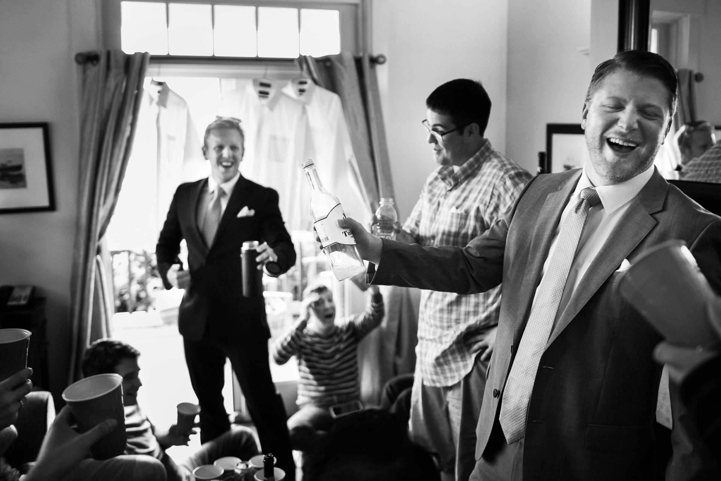 groomsmen laughing with drinks